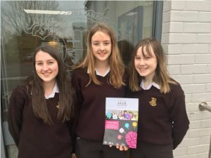 Loreto Letterkenny pupils holding card with AILO displayed.
